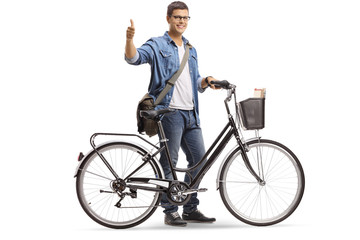 Young smiling man standing with a bicycle and giving thumb up