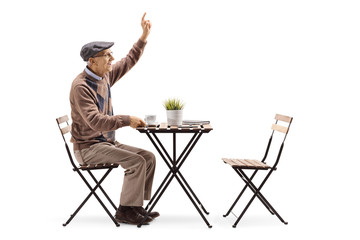 Elderly man sitting at a coffee table and calling a waiter