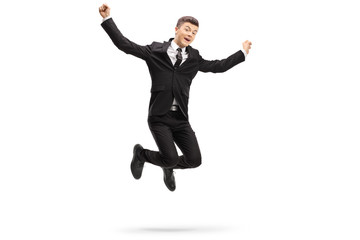 Elegant young man in a suit jumping