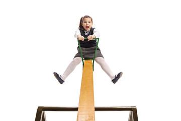 Cute little schoolgirl on a seesaw