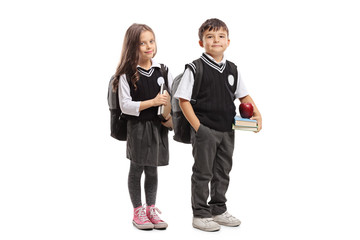 Schoolgirl and schoolboy in a uniform holding books and posing