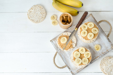Healthy breakfast with rice cakes with peanut butter and slices of banana on white wooden table. Space for text. Top view food.
