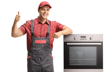 Smiling handyman in a uniform standing next to an electric oven ang giving thumbs up