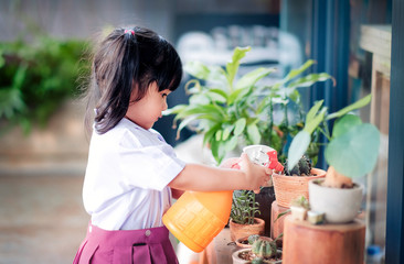 Happy Cute Asian Girl Enjoying with Gardening Activities, A Three Years old Child in Student Uniform is Watering Plant in the Garden, Happiness Moment
