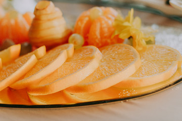 Exquisite cutting of fruit on the holiday table. Bright and colorful tartlets and canapes with oranges, tangerines, grapes and other fruits.