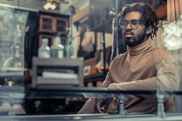Fototapeta Attentive international male person sitting in cafe