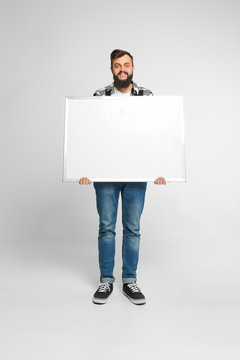 Positive smiling man wearing blue jeans and shirt with dark hair, beard, toothy smile is holding white big mockup poster isolated on white background