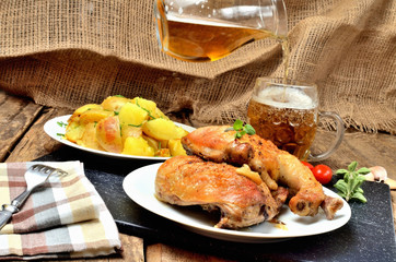 Grilled chicken legs on a plate, roasted potatoes and pouring cold beer into a glass, rosemary, tomatoes, oregano, salt, pepper and garlic on a wooden table