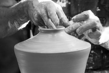 Detail of artist potter in the workshop sculpting ceramic vase, black and white