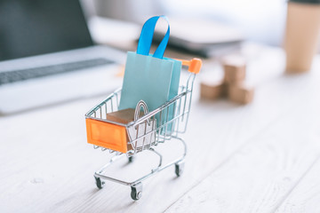 selective focus of decorative package and shopping bag in cart on wooden desk
