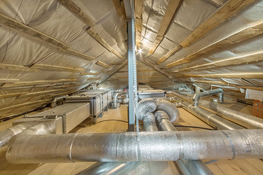 Whole house air ventilation and cleaning system. Ventilation pipes in silver insulation material on the attic