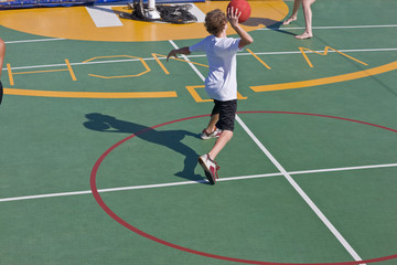 Teenage boy throwing a ball on a sports court.