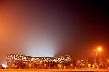 Illuminated sports stadium at night.