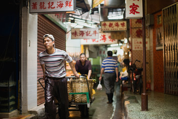 City workers walking through a narrow alleyway in the city at night.