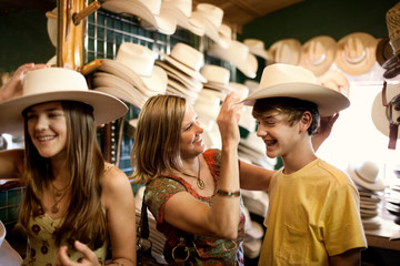 Smiling mother and teenage children trying on cowboy hats.