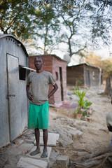 Portrait of a mature adult man standing beside a tin house.