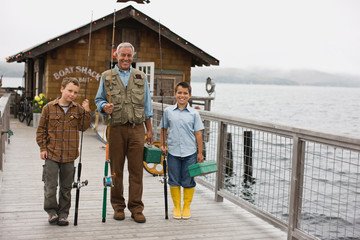 Portrait of a smiling father standing with his two sons on a wharf while holding fishing gear.