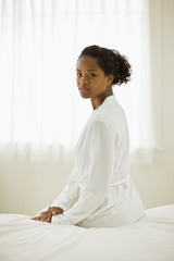 Portrait of a young woman sitting on a bed wearing a white robe