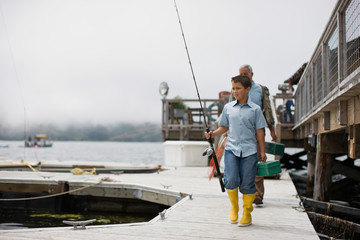 Boy walking along a jetty carrying fishing equipment with his father.