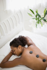 Young woman lying in bed on her stomach with healing stones on her back inside her bedroom.