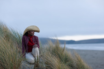 Mid adult woman wearing a sunhat while sitting in tussock grass on a remote beach.