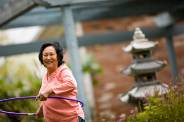 Older woman playing with hula hoop
