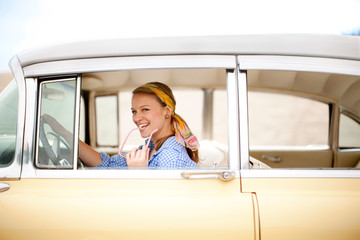 Young woman in 1950s outfit driving a vintage car