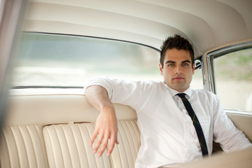 Young man in 1950s outfit in backseat of a classic car