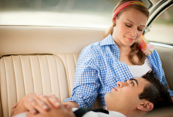 Young adult couple sitting in the back seat of a car.