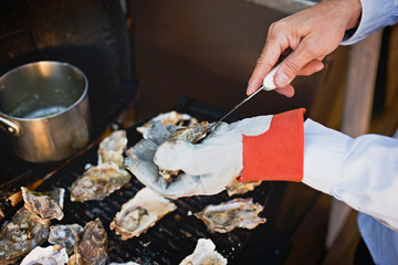 Person cutting open an oyster for grilling