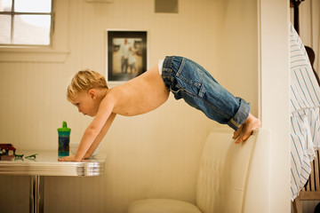 Little boy balancing on table