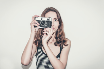 Nice girl in a striped t-shirt with a vintage camera in her hands. Photographing people.