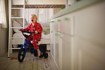 Little boy riding bike with training wheels