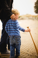 Father and son holding baseball bat on the beach