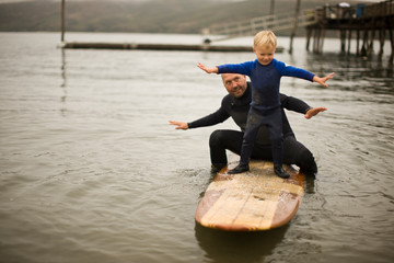 Father and son playing on surfboard.