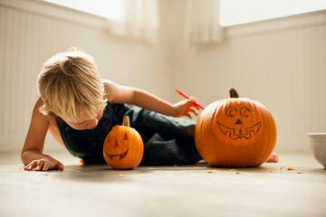 Young boy lies on his side and looks down at a small Jack O'Lantern next to a big,  uncarved pumpkin with a face drawn on it.
