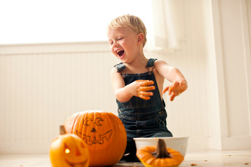 Young boy laughs as he holds out his hands covered in pumpkin flesh over a bowl with a big pumpkin with a face drawn on it and a finished small Jack O'Lantern with a candle lit inside in front of him.