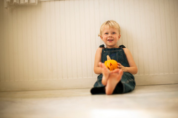 Young boy holds a small Jack O'Lantern on his knees as he sits on a floor leaning against a wall and poses for a portrait.