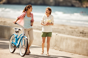 Two female friends walking along the coast,  walking a bicycle.