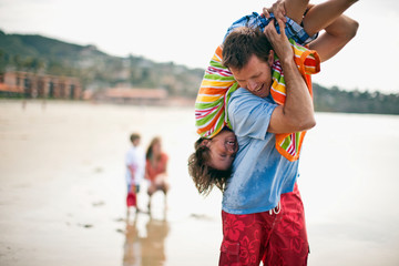 Father carrying his son upside down,  over his shoulder at the beach.