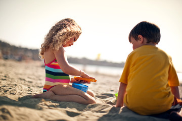 Brother and sister making sandcastles at the beach.
