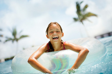 Portrait of a laughing girl floating in an inflatable ring in a swimming pool.