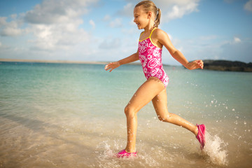 Happy young girl running in shallow water at a beach while wearing a bathing suit.