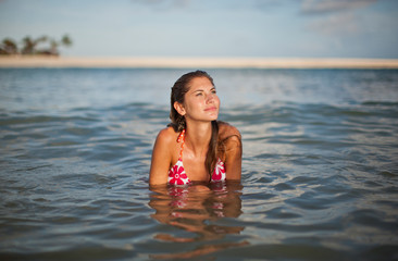 Daydreaming young woman swimming in the sea on a beach.