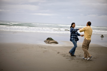 Mature man and woman dancing on the beach