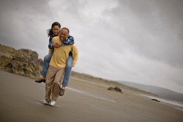 Mature man carrying a woman on the beach