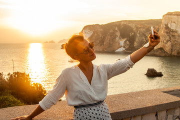 Young woman with smartphone taking selfies with sunset in front of the sea on Ponza island coast, on a wall with view of the ocean.