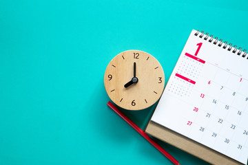 close up of calendar, clock and pencil on the table, planning for business meeting or travel planning concept