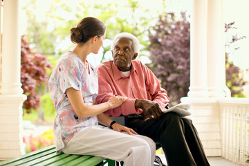 Nurse and a senior man in a wheelchair talk as they sit together on a porch.