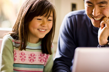 Father and daughter smile while working on a laptop together.